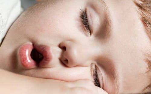 Rebenok spit s otkrytym rtom
